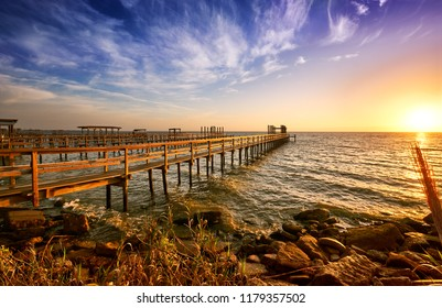 Long wooden docks reach into Galveston Bay, Texas, at dawn