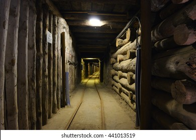 Long wooden hallway in mineshaft  with railroad tracks