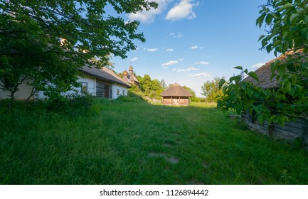 a long wooden house with stables on the overgrown grass of the yard. Uzhhorod Ukraine