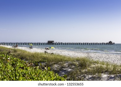 Long wooden pier of caribbean beach of Naples in Florida
