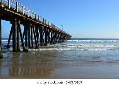 Long wooden pier with clear blue skies in background