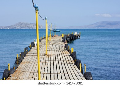 A long wooden pier with yellow pillars on the background of blue sea summer day.