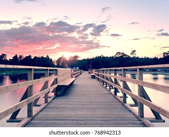 Long wooden sea bridge on coast during morning. Cold weather with first sun rays at horizon, smooth water. New built  pier in summer holiday resort. Empty mole.
