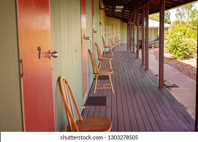 A long wooden shady verandah in front of rooms to rent at a farm stay in Australia
