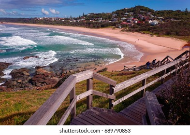Long wooden strairs to an Australian beach on the pacific ocean. Wide stretch of sand on the east coast of Australia. Lighthouse Beach in Port Macquarie.