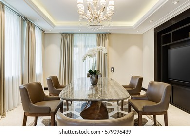 Long wooden table and many chairs around, room for big family. Classic interior of dining room in brown, white, beige colors, with crystal chandelier in the center of ceiling. Orchid of table.