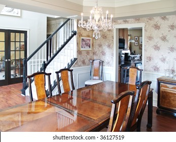 A long wooden table in a modern American luxury home. Six dining room chairs surround the table, and the stairs and foyer are visible in the background.