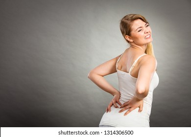 Long working hours and health. Young female with backache. Woman suffering from back pain on gray