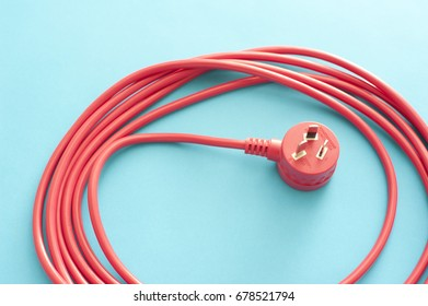 Long wound up red extension cord over blue background. Australian type plug receptacle.