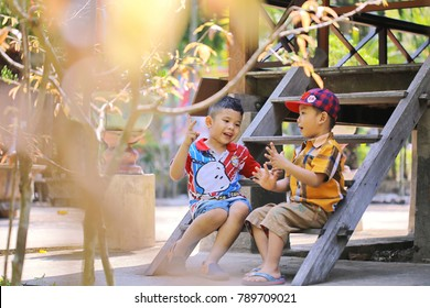 Long Xuyen city, Vietnam - January 31, 2016: Two litle boys sitting on wooden stair playing One - Two - Three game together