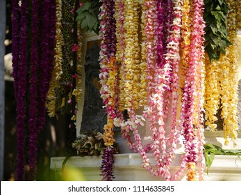 Long yellow pink flowers lei hanging on a king kamehameha statue in Honolulu Hawaii