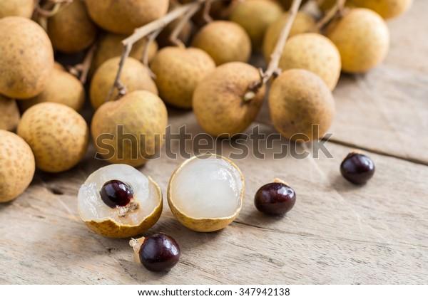Longan Fresh (Dimocarpus longan.) Un mazzo di Longan e Peel mostrano che la carne bianca con seme nero è stata posta su uno sfondo di legno.