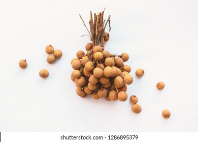 Longan fruit or dragon eye fruit in branch on dark background. Super food tropical local product of Thailand and China. Top view flat lay