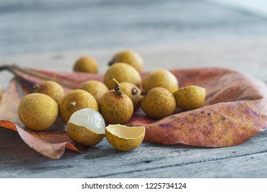 Longan fruits and shell on red leaves on a wooden table