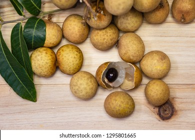 The Longan is a tropical tree. The fresh longans with the green leaves. Longans with wood background.Fresh ripe longan and peel show the white meat.