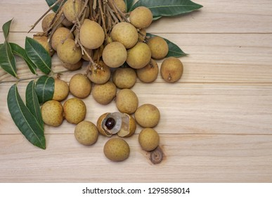 The Longan is a tropical tree. The fresh longans with the green leaves. Longans with wood background.