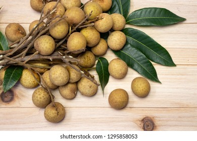 The Longan is a tropical tree. The fresh longans with the green leaves. Longans with wooden background.
