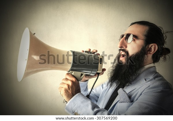 Long-bearded businessman screaming into a megaphone