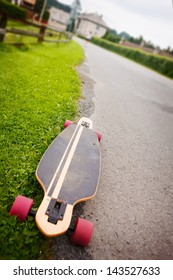 Longboard by the asphalt road at the border of a village.