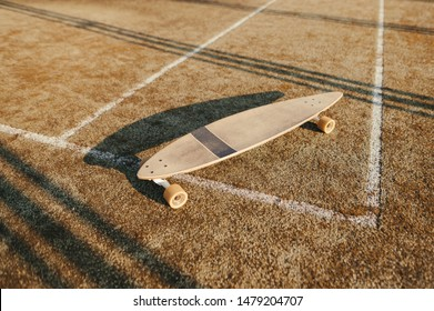 Longboard on old tennis floor. Longboard stands on a brown background. Background. Closeup photo of one skateboard and artificial turf cover.Longboarding concept. Copy space