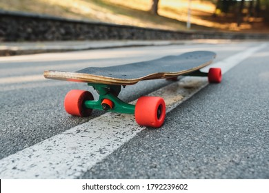 Longboard with red wheels on the asphalt. High quality photo