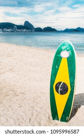 Longboard surfboard with a Brazilian flag standing on the sand overloooking the coastline of Copacabana Beach, Rio de Janeiro, Brazil.