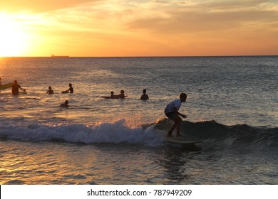 Longboard surfer riding a small wave at sunset in front of a crowd of swimmers at City Beach, Perth, Western Australia