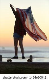 Longboarder riding holding american flag at sunset, summer holiday 4th july celebrations