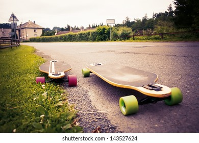 Longboards by the asphalt road at the border of a village. Toned image.