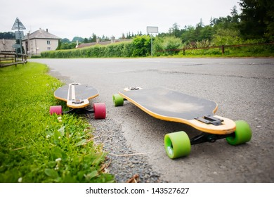 Longboards by the asphalt road at the border of a village.