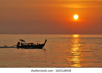 A longboat in Thailand heading back during sunset.
