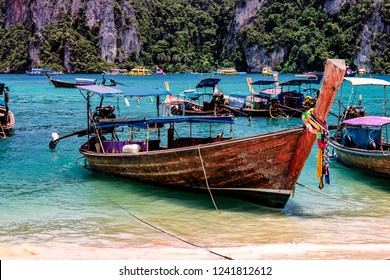 A longboat tied and pushed up onto the beach far enough it is grounded and wont float away and rope tying it off. Other vessels occupy the surrounding bay. Paradise at Phi Phi Island, Thailand.