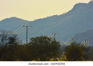 Long-distance powerlines at the foot of the Macdonnell Range in Central Australia transmits electricity to remote cattle stations and communities.