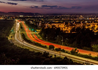 Long-exposure light streaks of traffic at dusk over a busy road in Playa Vista, California