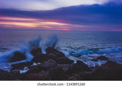 Long-exposure photograph of silky smooth water flowing around rock formations after sunset at Point Dume State Beach with clouds in the sky, Malibu, California
