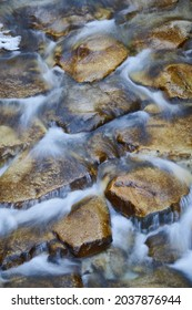 A longexposure photography of the stream of a river and the rocks