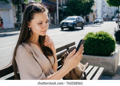 long-haired attractive girl sitting on a wooden bench on the street, doing selfie