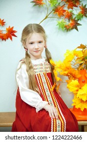 long-haired blue-eyed blonde girl sitting on a bench in a Russian folk red sundress and a white blouse on the autumn festival in the kindergarten on the background of decorative colorful leaves