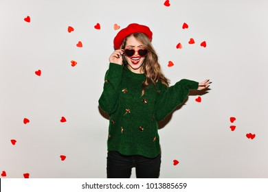 Long-haired enchanting girl in french beret making funny faces on white background. Unpleased brunette female model in black sunglasses standing under heart confetti.