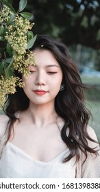 Long-haired gentle girl standing under the sweet-scented osmanthus tree