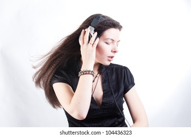 long-haired girl enjoys music with a ear-phones