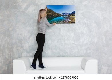 Long-haired girl hanging pictures in frames on wall at house