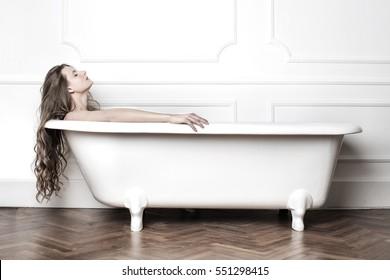 Long-haired girl having a bath in a white bathtub