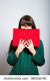 long-haired girl hides behind the book, a student in isolation on a gray background