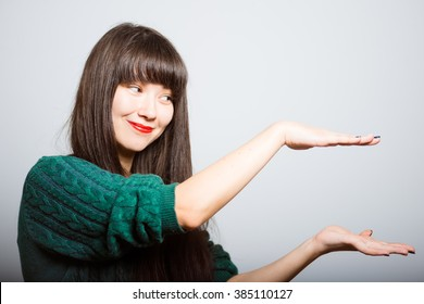 long-haired girl holding something invisible on the palms, business woman isolated on a gray background