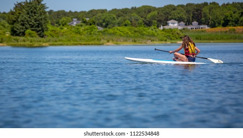 Longhaired girl paddles across pond in Martha's Vineyard
