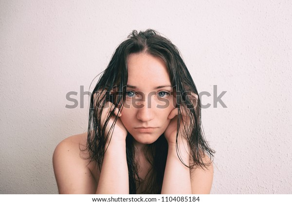 a long-haired girl touching her face with her hands