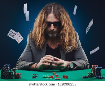 Long-haired handsome man playing poker in a casino. Studio concept on blue background