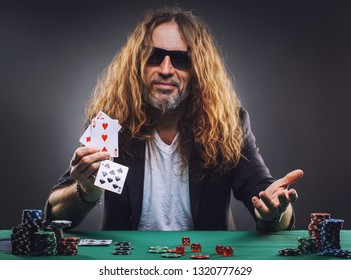 Long-haired handsome man playing poker in a casino. Studio concept on gray background