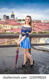 long-haired lass wearing blue short skirt and blouse with bright umbrella stands on the roof of the building